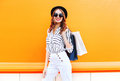 Fashion pretty young smiling woman model with shopping bags wearing a black hat white pants over colorful orange Royalty Free Stock Photo