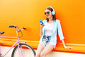 Fashion pretty young woman listens to music using smartphone near urban retro bicycle over colorful orange