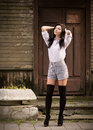 Fashion pretty young woman posing outdoor near a old wooden wall beautiful brunette with sensual lips in stockings Royalty Free Stock Photography