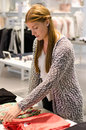 Fashion retail store saleswoman a folding clothes in a boutique for women Royalty Free Stock Photos