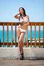 Fashion shoot a beautiful girl in a white swimsuit on the sea background Royalty Free Stock Photo