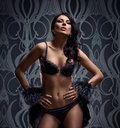 Fashion shoot of a young brunette in dark lingerie Royalty Free Stock Photos