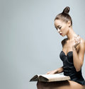 Fashion shoot of a young woman reading a book Stock Image