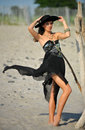 Fashion shot of brunette young girl in black luxury dress and hat posing on the beach Stock Image