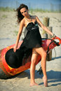 Fashion shot of brunette young girl in black luxury dress posing on the beach with bouy on the background Royalty Free Stock Photography