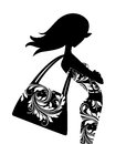 Fashion silhouette of a chic young woman with a large handbag posing in profile Stock Photos