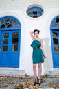 Fashion slim woman standing against old destroyed store wearing green strapless short dress with broken glasses full length body Royalty Free Stock Images