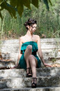 Fashion slim woman wearing green strapless short dress sitting on old and dirty cement stairs Royalty Free Stock Photo