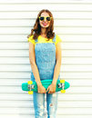 Fashion smiling woman with a skateboard posing over white background Royalty Free Stock Photo