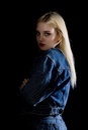 Fashion studio photo of young woman in danim jacket on dark background