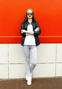 Fashion stylish pretty woman wearing a rock black leather jacket and sunglasses in city Royalty Free Stock Photo