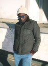 Fashion stylish young african man wearing a sunglasses and jacket with knitted hat Royalty Free Stock Photo