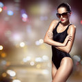 Fashion woman. Bikini and sunglasses. Night city background. Royalty Free Stock Photo