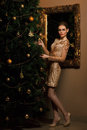 Fashion woman hanged a toy on the christmas tree stylized as gold Royalty Free Stock Photography