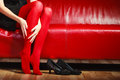 Fashion woman legs red pantyhose on couch elegant outfit fashionable long in vivid color black shoes sitting indoor Royalty Free Stock Photography