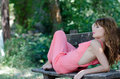 Fashion woman lying on bench with a pink piece garment back the wear nice romantic outdoor photo of girl in love skeptical for Royalty Free Stock Images