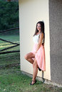 Fashion woman at ranch a young in a dress leaning on a wall Stock Images
