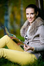 Fashion woman reading  magazine outside in evening park Royalty Free Stock Photo