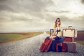 Fashion woman ready to leave sitting on her luggage phoning Royalty Free Stock Image