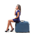 Fashion woman ready to leave sitting on her luggage phoning Royalty Free Stock Photography
