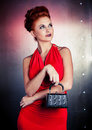 Fashion woman red dress with litle bag. Metal wall background Royalty Free Stock Photo