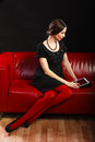 Fashion woman retro style with tablet technology internet business concept sitting on red couch Stock Image