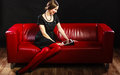 Fashion woman retro style with tablet technology internet business concept sitting on red couch Royalty Free Stock Image