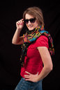 Fashion woman with sunglasses and scarf posing on black backgrou over background Royalty Free Stock Images
