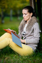 Fashion woman using a tablet computer outside in evening park student sitting on green grass over tree Stock Photos