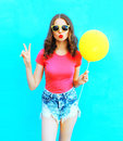 Fashion woman wearing a t-shirt, denim shorts with yellow air balloon over colorful blue Royalty Free Stock Photo