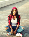 Fashion young african woman having fun in city, wearing red checkered shirt and baseball cap Royalty Free Stock Photo