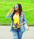 Fashion young african woman holds retro vintage camera wearing a jeans clothes and sunglasses in the city Royalty Free Stock Photo