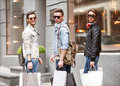 Fashion young guys go shopping with many colored bags in their hands watch purchase in the background window dressing Royalty Free Stock Images