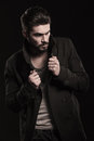 Fashion young man with beard pulling his coat's collar Royalty Free Stock Photography