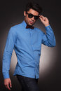 Fashion young man holding his fashionable sunglasses Royalty Free Stock Images