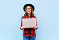 Fashion young smiling woman holding laptop computer in city, wearing black hat red checkered shirt over blue background Royalty Free Stock Photo