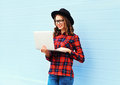 Fashion young smiling woman using laptop computer in city, wearing black hat, red checkered shirt Royalty Free Stock Photo