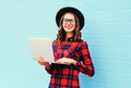 Fashion young smiling woman using laptop computer in city, wearing a black hat, red checkered shirt Royalty Free Stock Photo