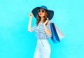 Fashion young smiling woman wearing a shopping bags, straw hat, white pants over colorful blue background posing in city Royalty Free Stock Photo