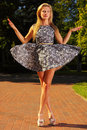 Fashion young woman in park stylized like marionet full length fashionable summer flowery dress outdoor relaxing marionette Royalty Free Stock Images