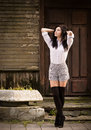 Fashion young woman posing near a old wooden wall pretty outdoor in stockings Royalty Free Stock Images
