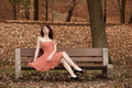 Fashion young woman in red dress relaxing in park on bench full length fashionable outdoor sitting vintage photo sepia tone Royalty Free Stock Photography