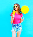 Fashion young woman wearing a t-shirt, denim shorts drinks fruit juice from cup with yellow air balloon over colorful blue Royalty Free Stock Photo