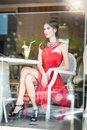 Fashionable attractive young woman in red dress sitting in restaurant beyond the windows beautiful brunette posing in restaurant Stock Photos