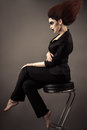 Fashionable beautiful business woman sitting on bar stool with lush hair Royalty Free Stock Photo