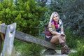 Fashionable blonde woman sitting in a park on an old wooden swing young Royalty Free Stock Images