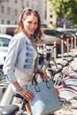 Fashionable brunette young woman sitting on bicycle Royalty Free Stock Photo