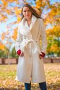 Fashionable confident young woman wearing a stylish white overcoat and red mittens standing outdoors in a colorful autumn park Royalty Free Stock Image