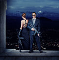Fashionable couple with automatics women and men holding Stock Photos