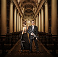 Fashionable couple with automatics women and men holding in church Stock Photo